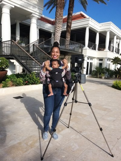 Femal entrepreneur standing next to a camera and carrying a baby on the film set.